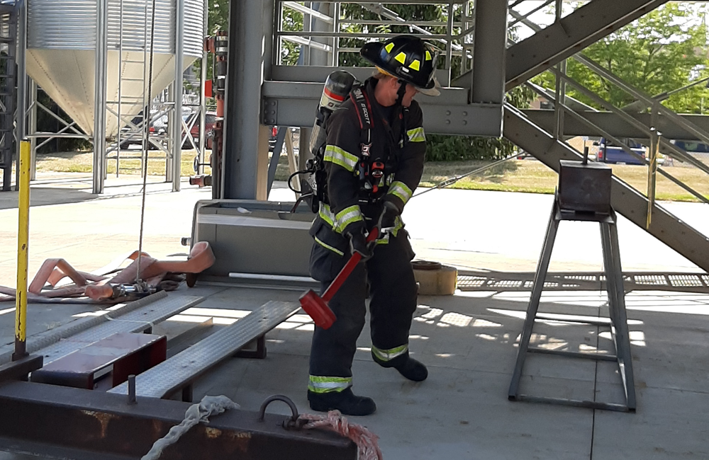 Auburn firefighter using a sledgehammer during a forcible entry stimulation.